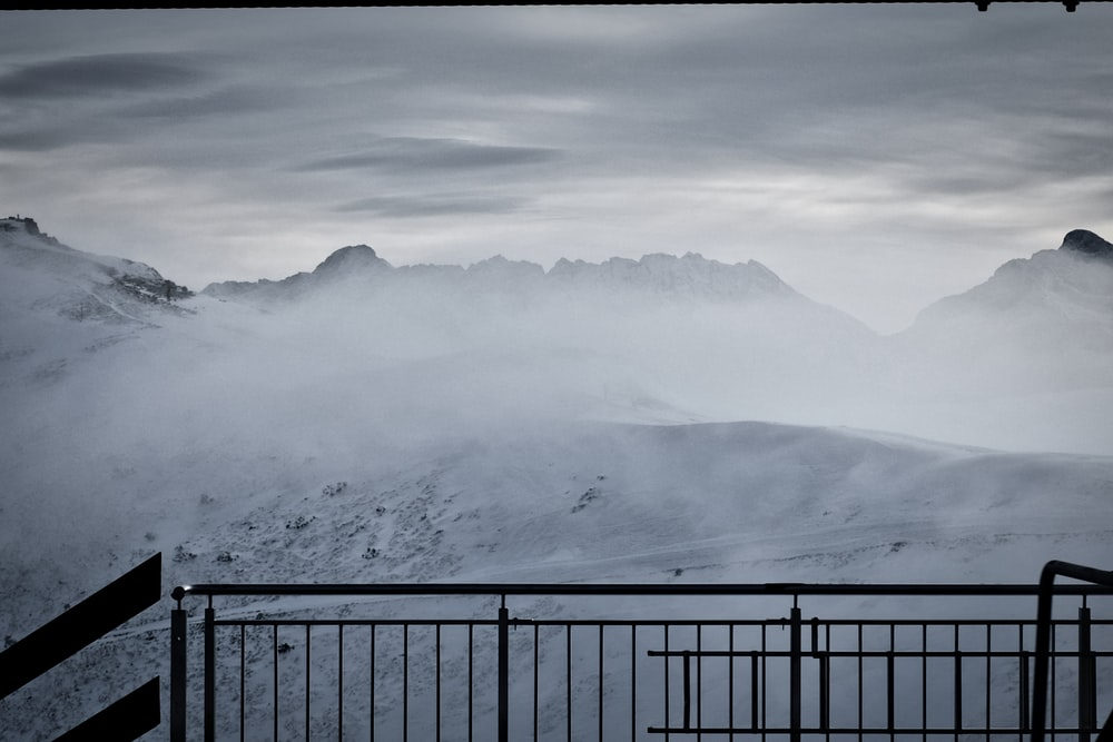 black metal fence near snow covered mountain during daytime