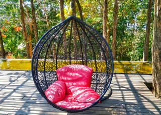 red and white floral hammock on brown wooden floor