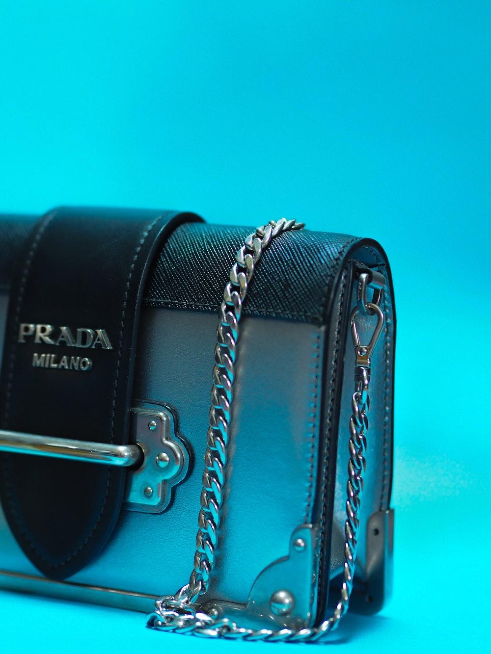 black leather handbag on teal surface