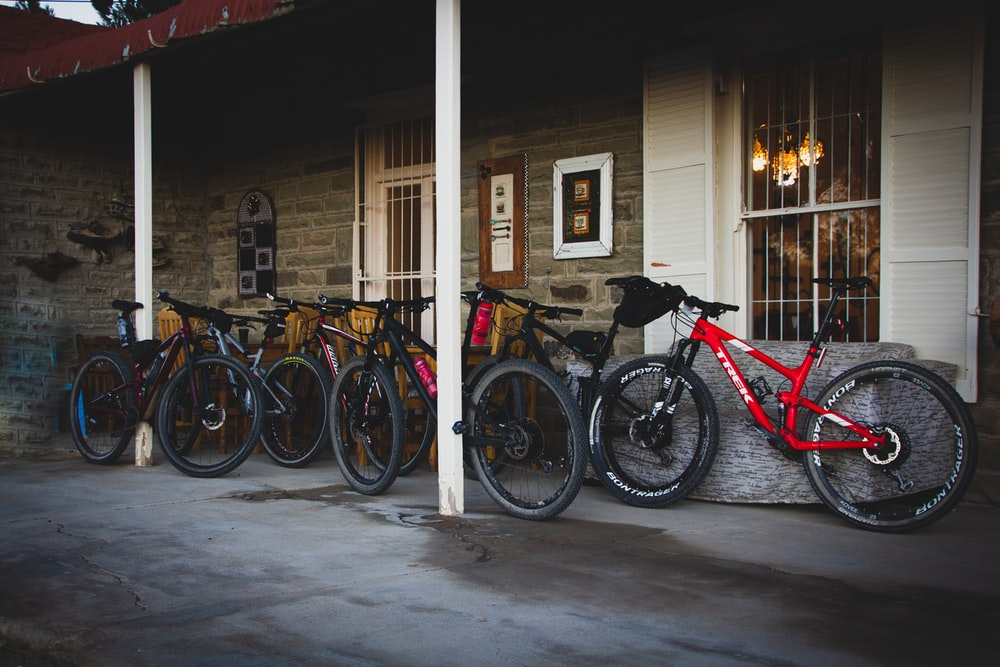 red and black bicycles parked beside brown wooden house during daytime
