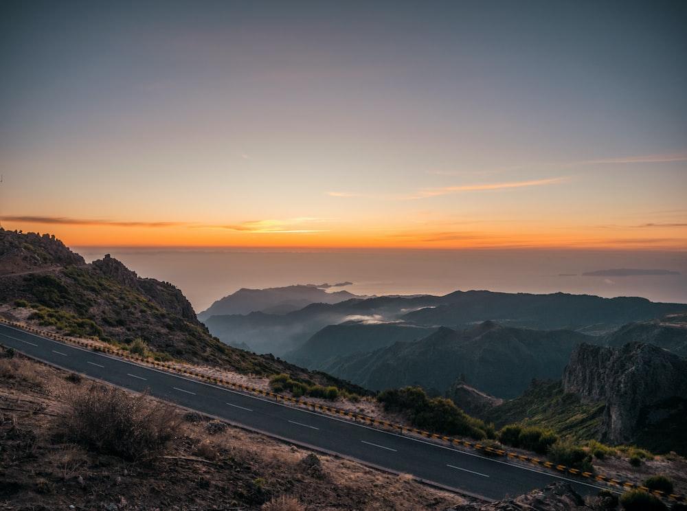 black asphalt road near mountains during sunset