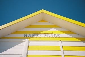 """A striped yellow and white English beach hut with the name of """"Happy Place"""". A dark blue sky is in the background. Shot on film."""