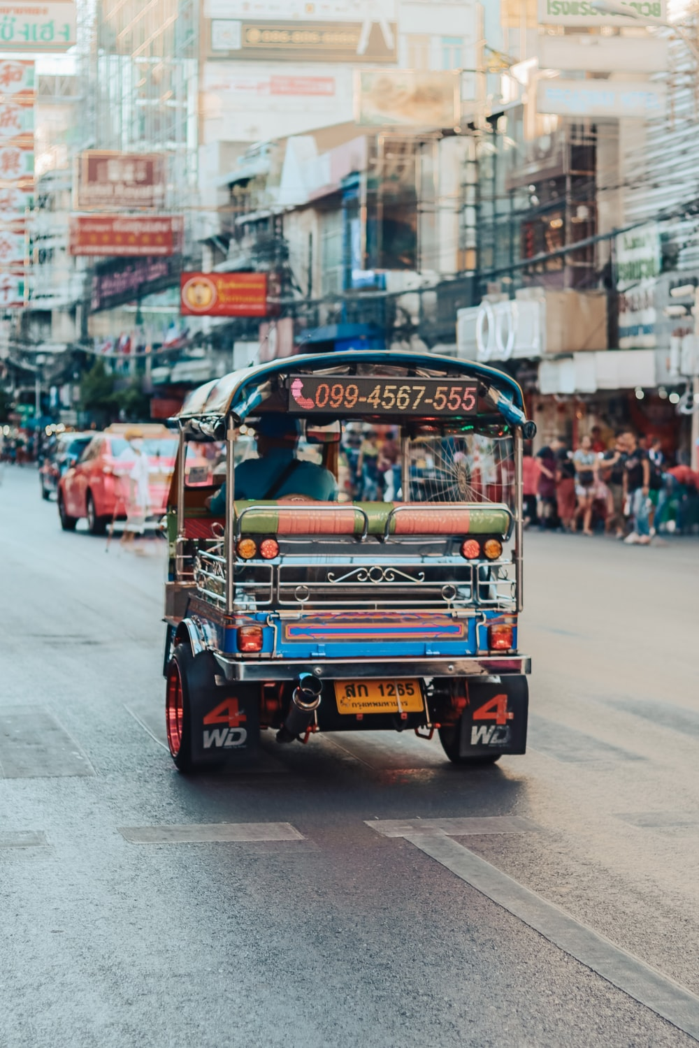 red and blue auto rickshaw on road during daytime