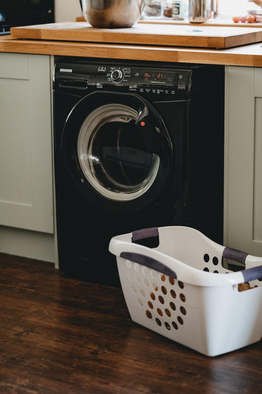 white plastic laundry basket beside black front load washing machine