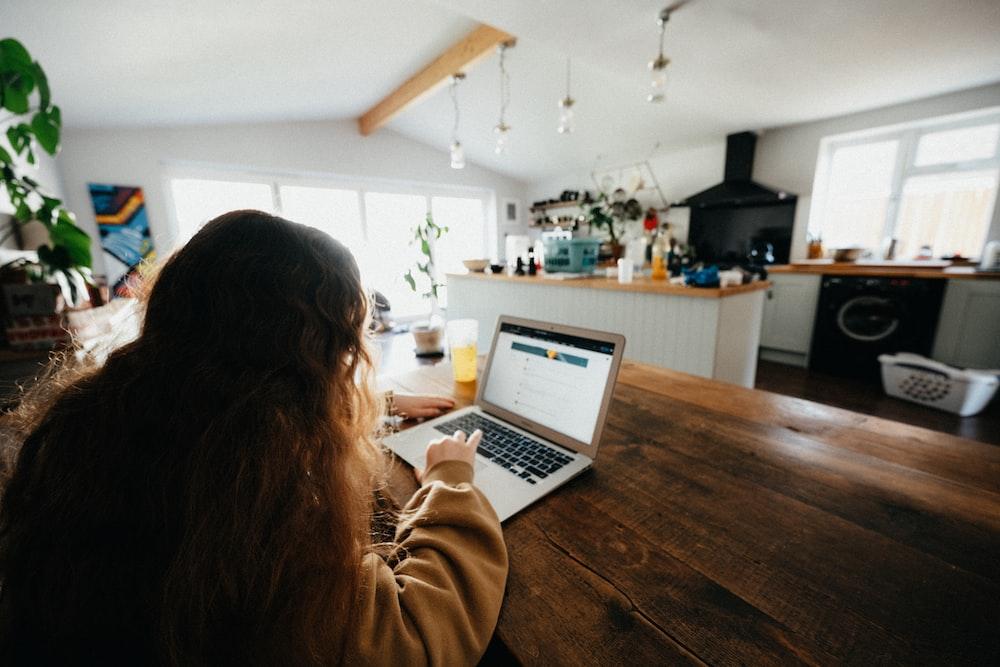 woman in brown sweater using macbook pro