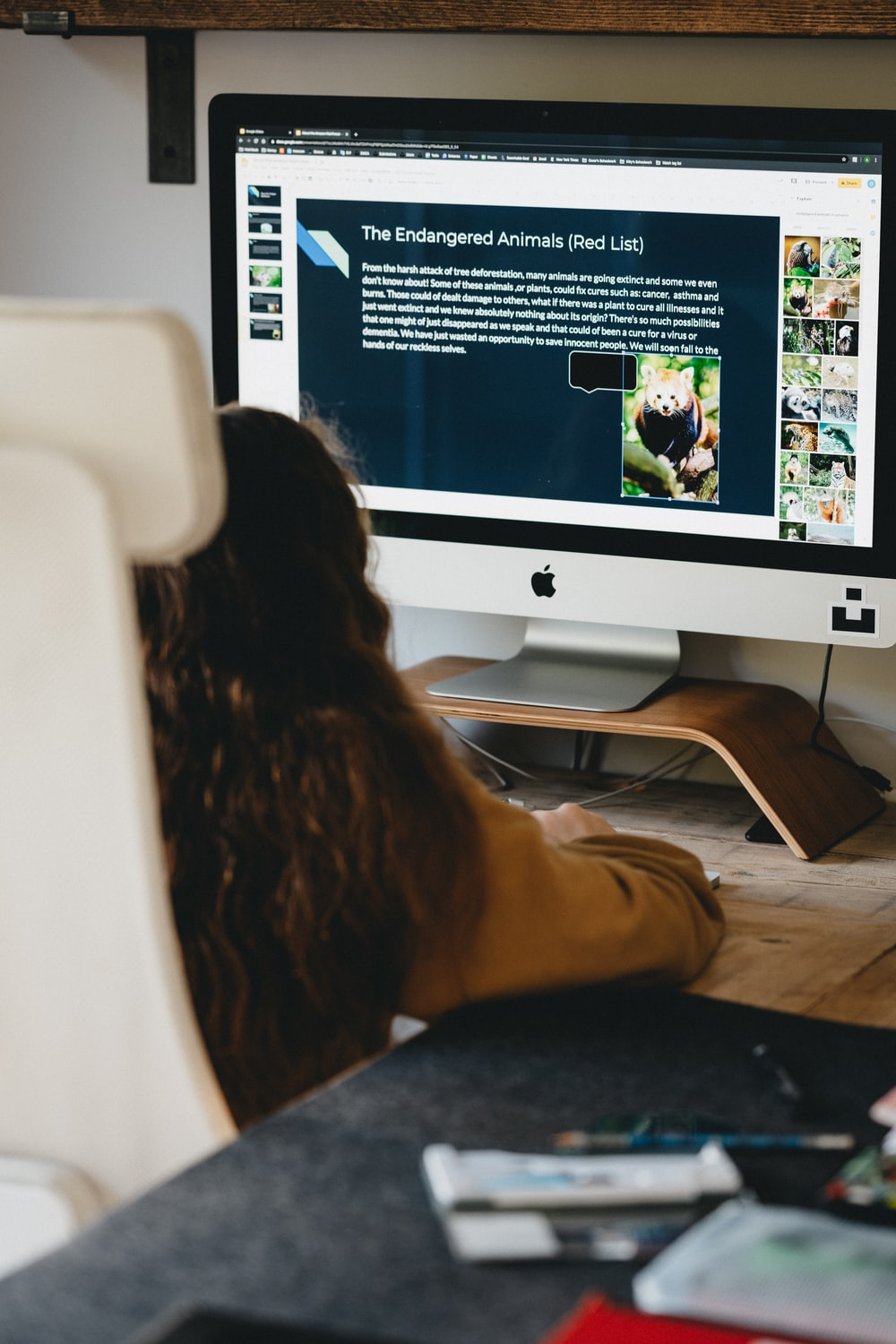woman in black shirt sitting in front of silver imac