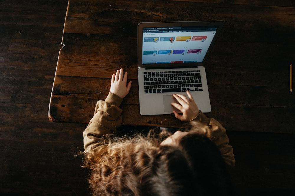 person using macbook pro on brown wooden floor