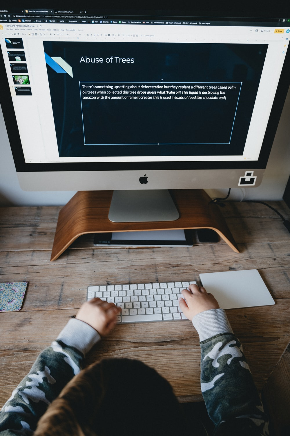 person in gray long sleeve shirt using silver imac