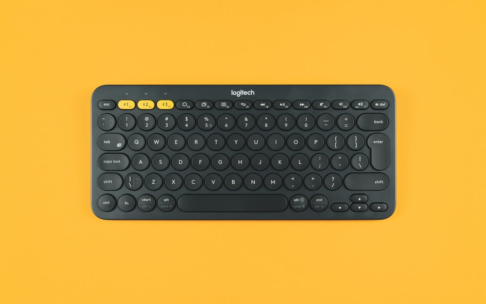 black logitech keyboard on orange surface