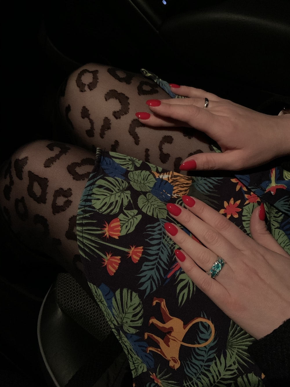 person wearing silver ring and black red and green floral pants