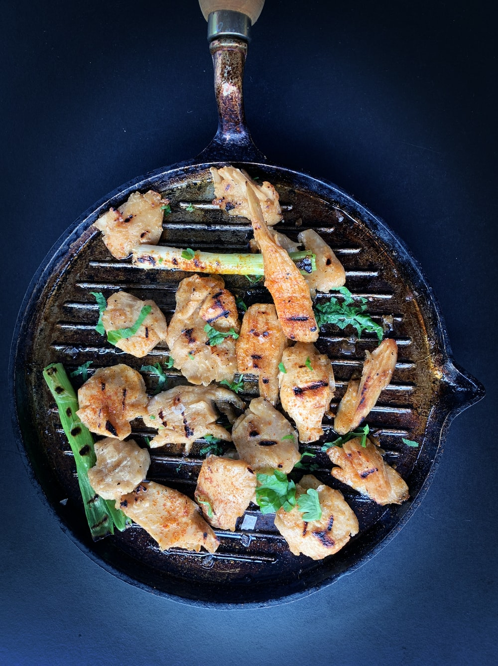 fried meat with green vegetable on black pan