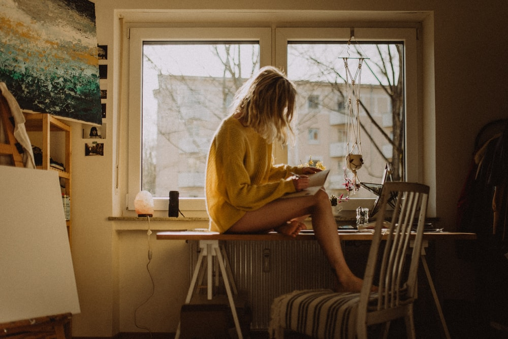 woman in yellow sweater sitting on chair