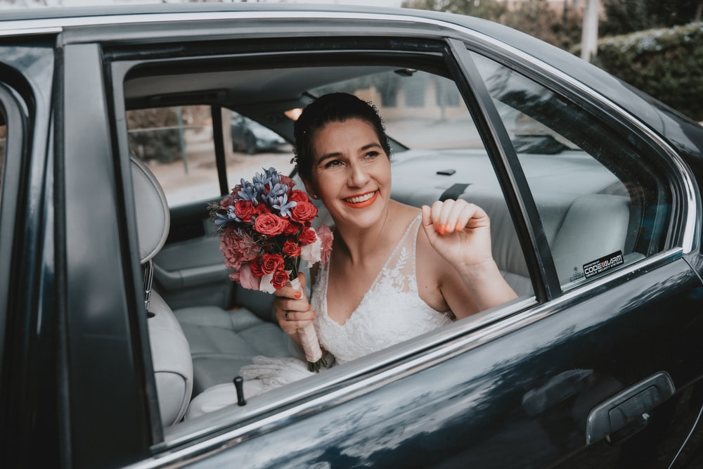 woman in white wedding dress holding bouquet of flowers inside car