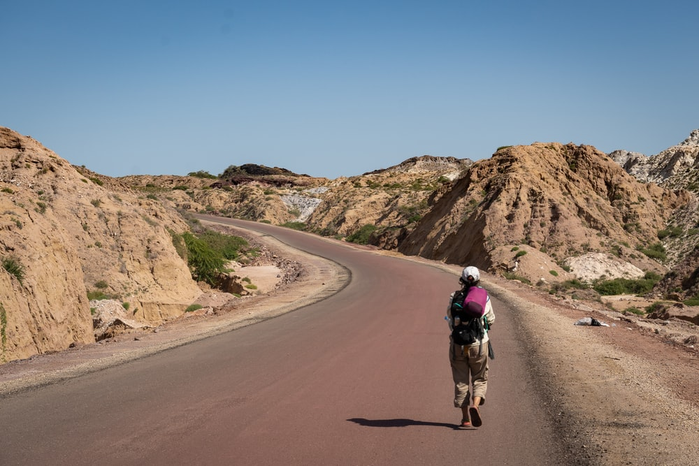 man in black jacket riding on brown horse on brown dirt road during daytime