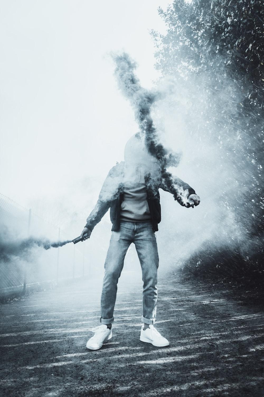 man in white shirt and black pants holding smoking pipe