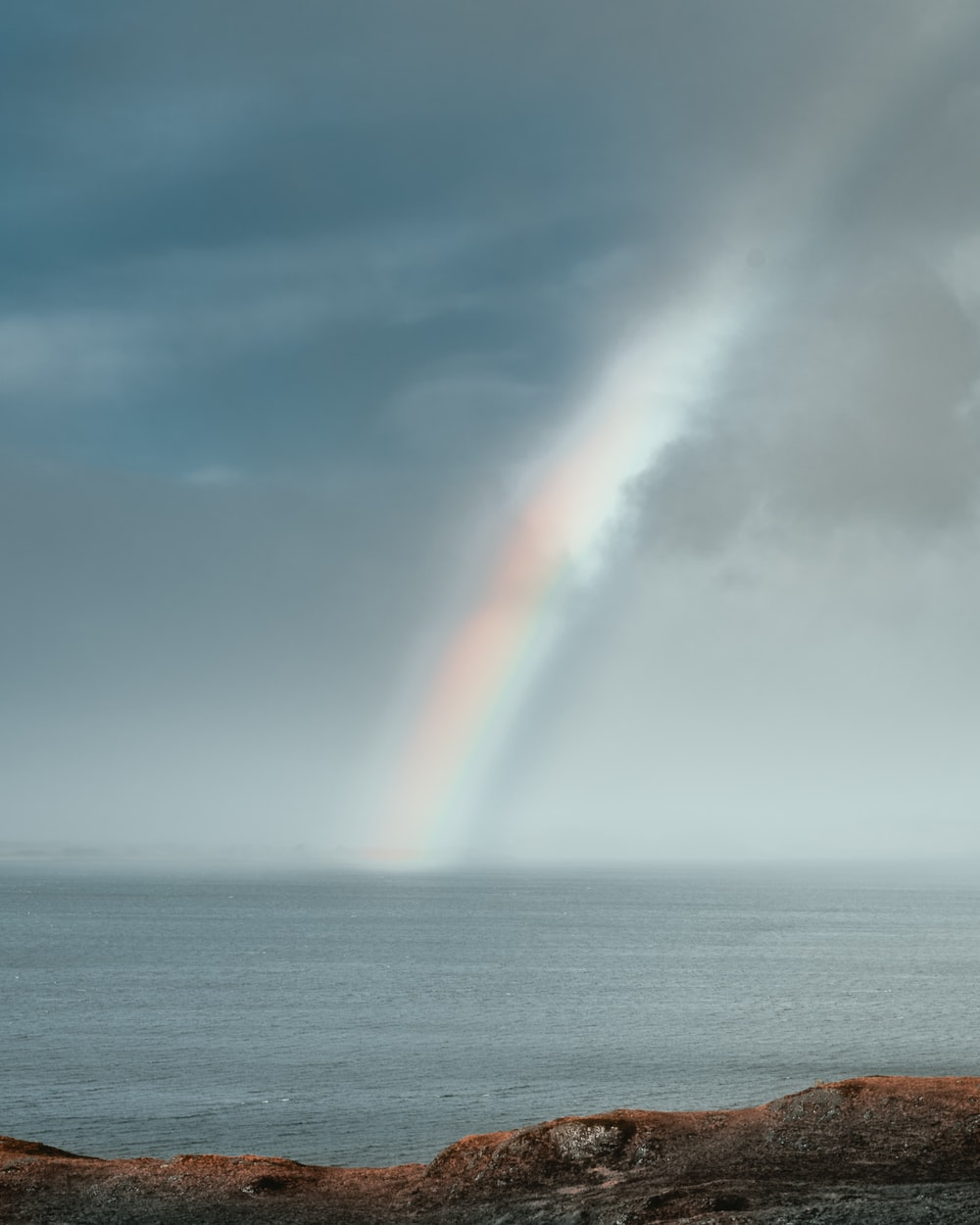 rainbow over the sea during daytime