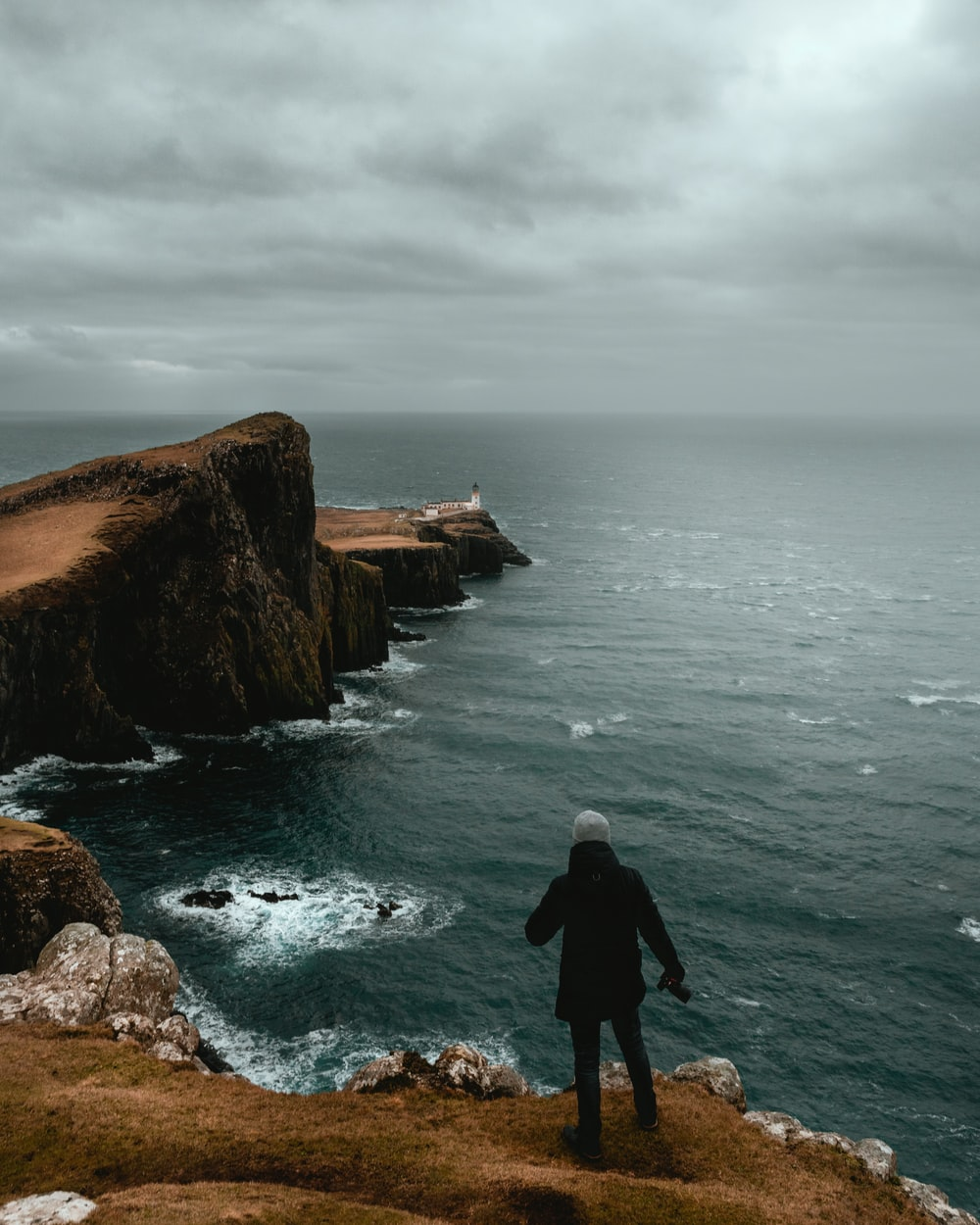 man in black jacket standing on brown rock formation near body of water during daytime