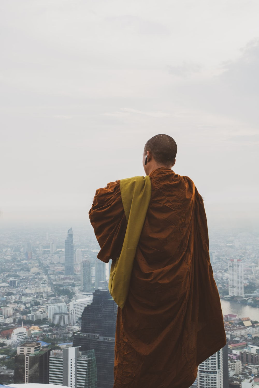 man in brown robe standing on top of building during daytime