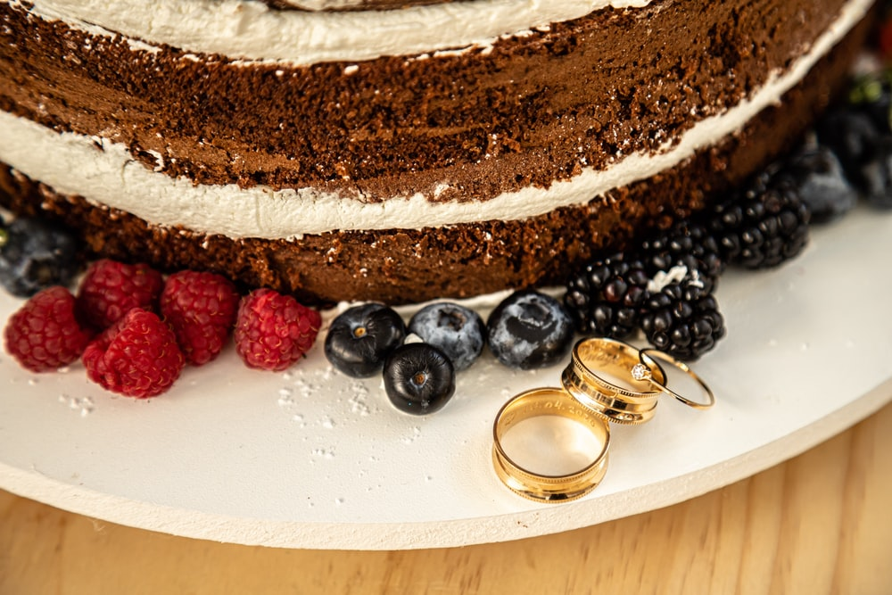 chocolate cake with raspberry and blueberry on white ceramic plate