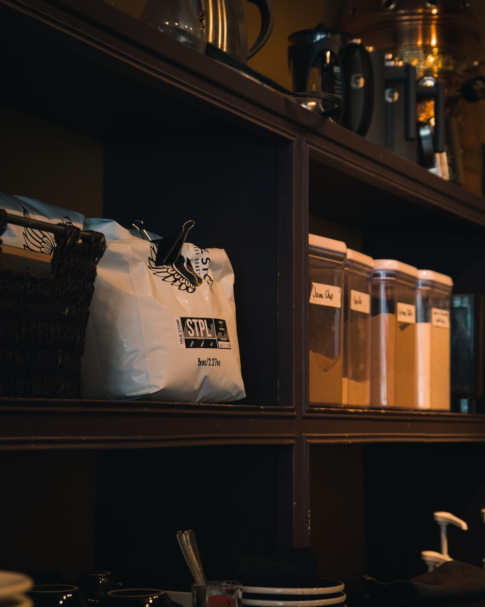 white and black plastic bag on brown wooden shelf