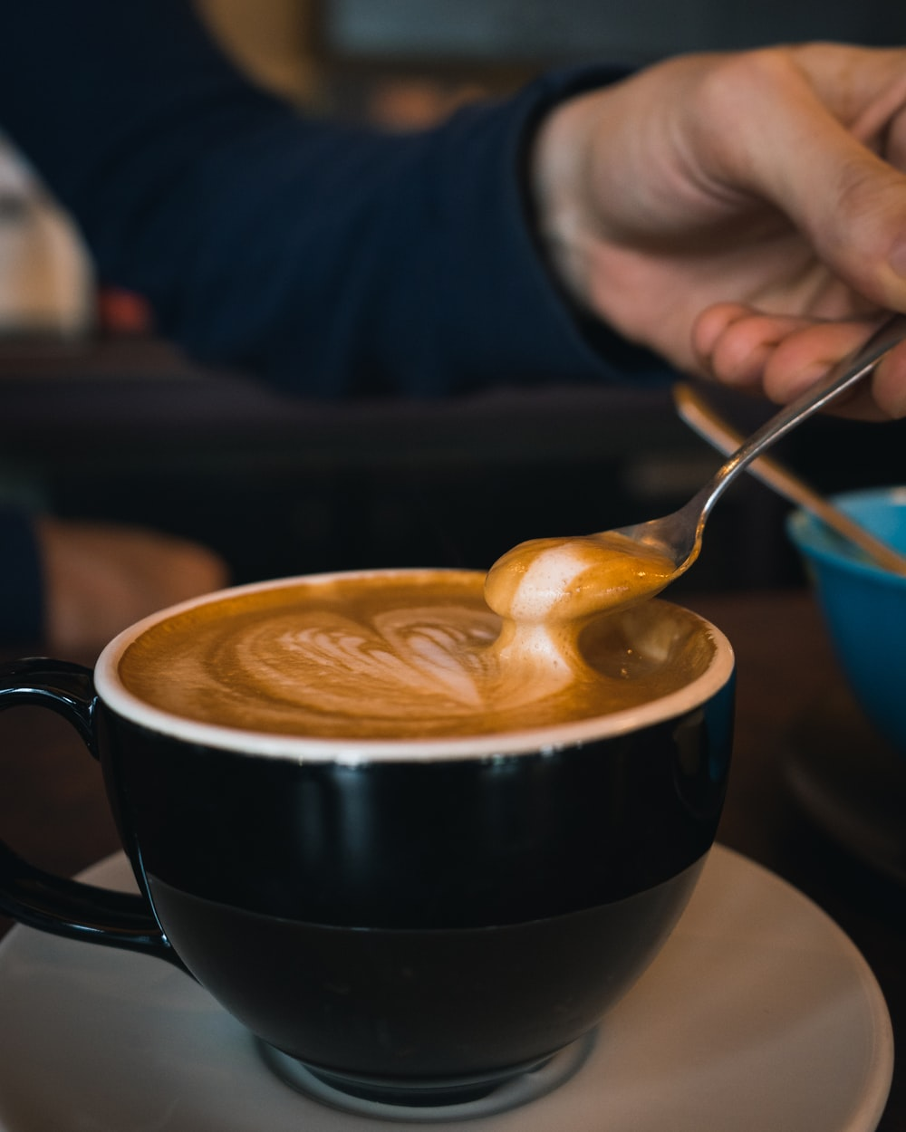 person holding silver spoon and black ceramic mug with cappuccino