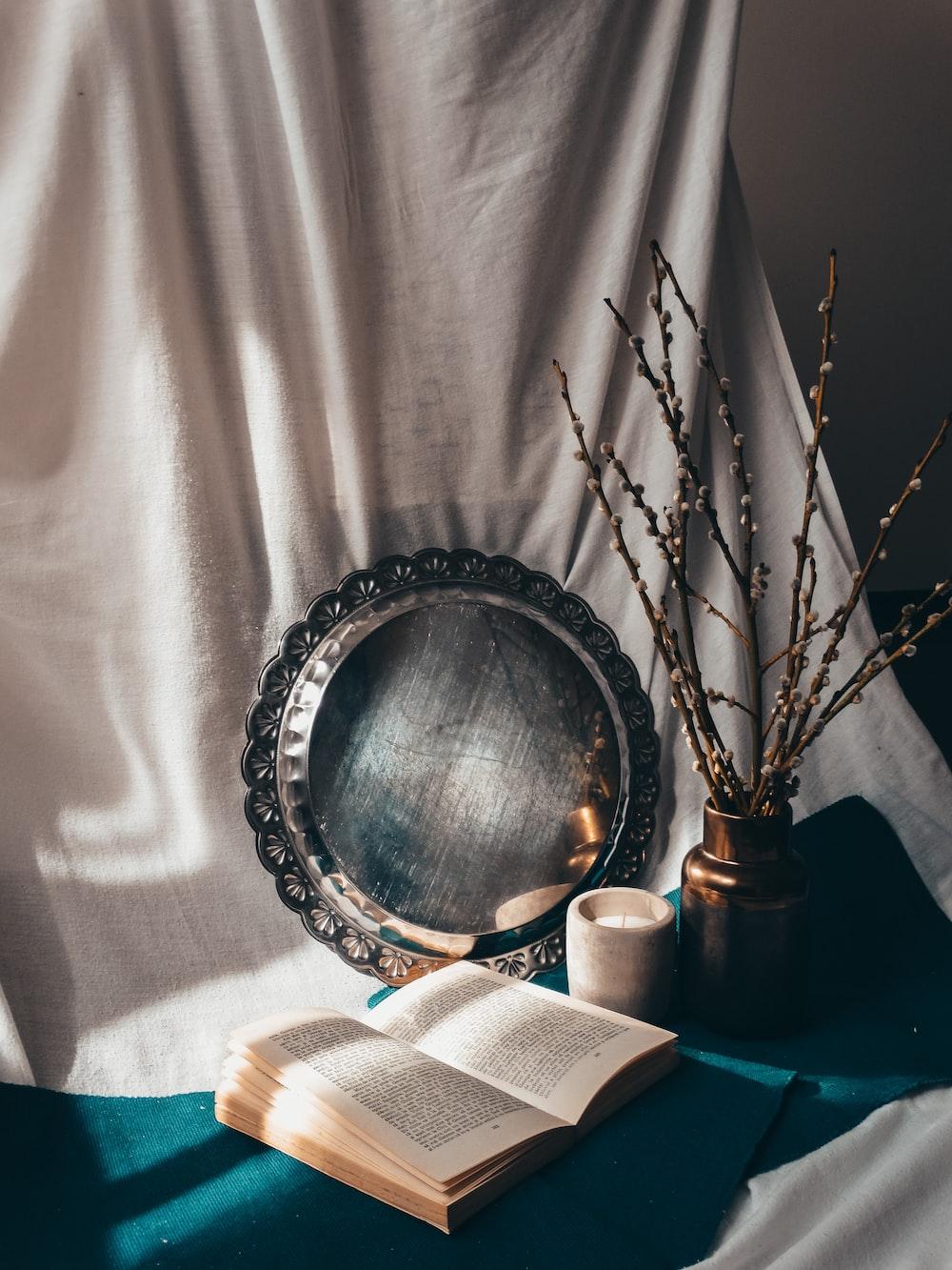 silver round framed mirror on white textile