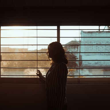 woman in white and black stripe shirt standing near window