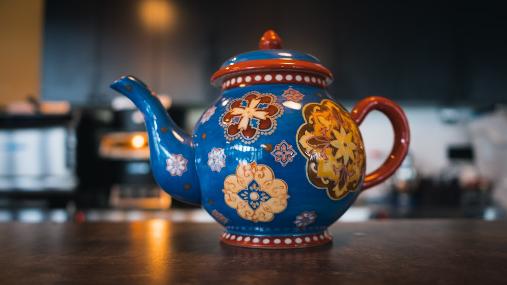 blue and brown ceramic teapot on brown wooden table