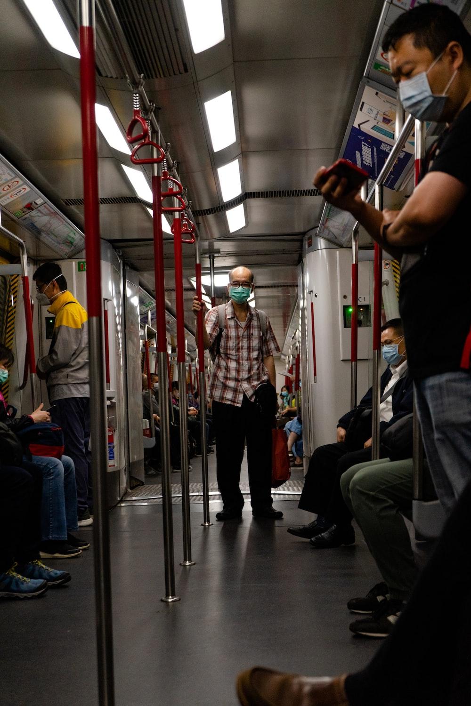 黒いタンクトップと電車の横に立っている黒いズボンの男