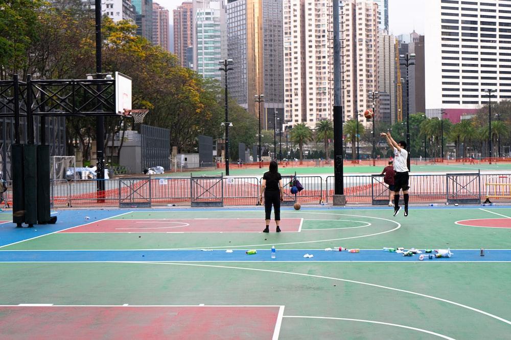 people playing basketball on basketball court during daytime