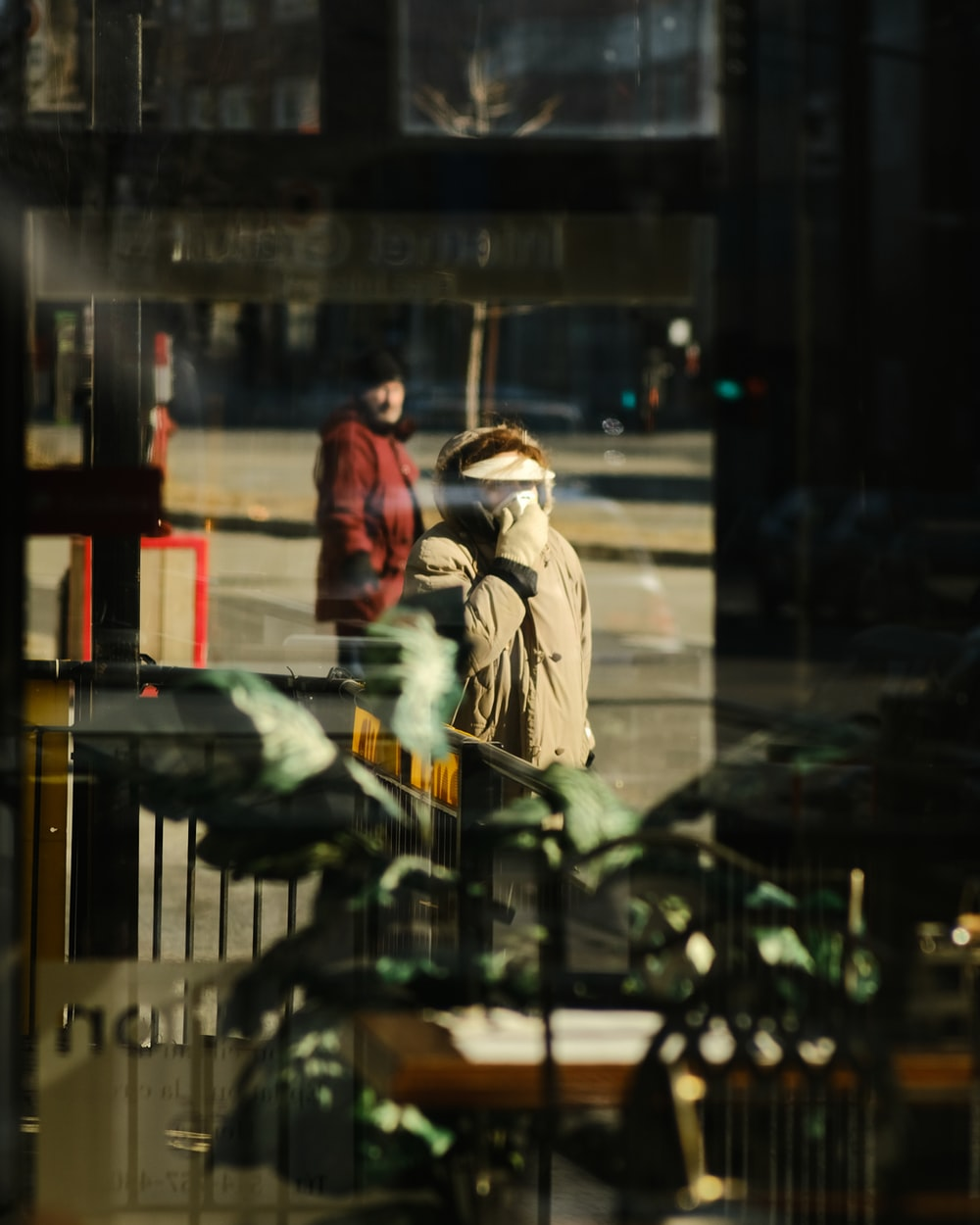 woman in brown coat standing in front of glass window