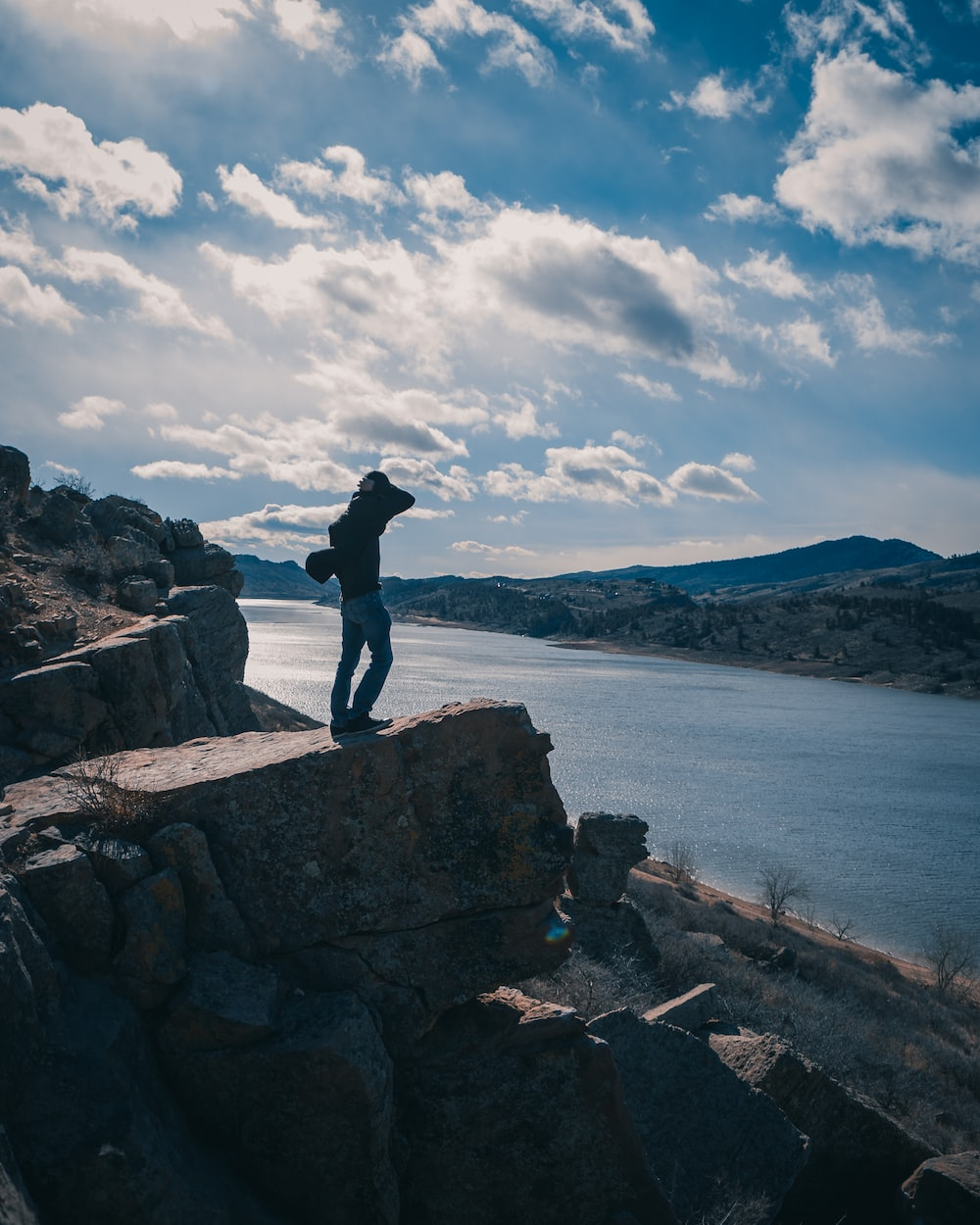 man in black jacket standing on rock near body of water during daytime