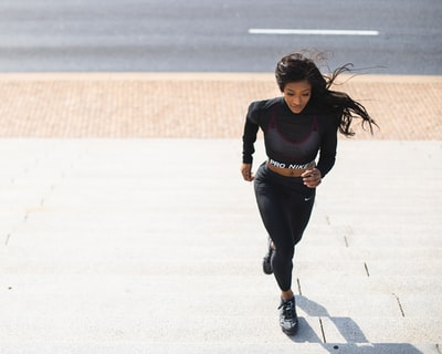 woman in black long sleeve shirt and black pants running on gray concrete road during daytime lincoln memorial teams background