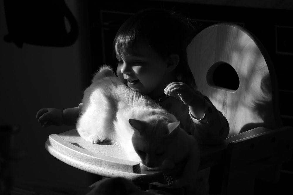 grayscale photo of girl kissing cat