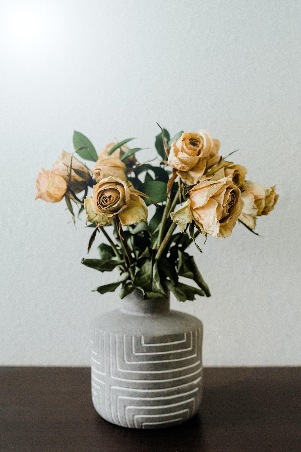 white and yellow roses in white ceramic vase