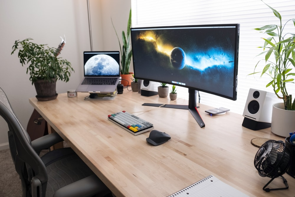 black flat screen computer monitor on brown wooden desk