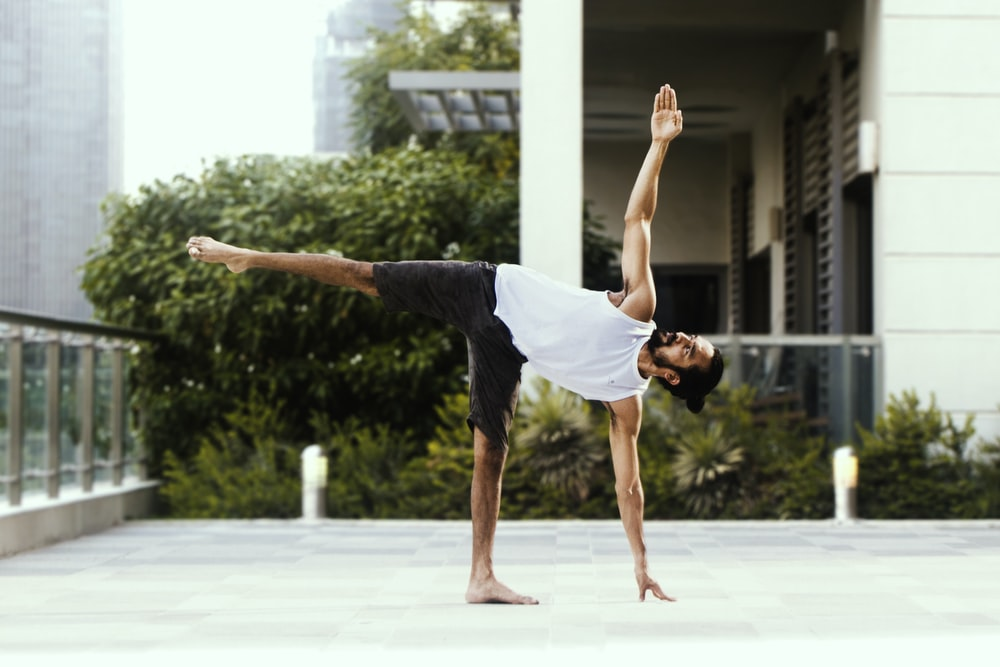 man in white tank top and black shorts doing yoga