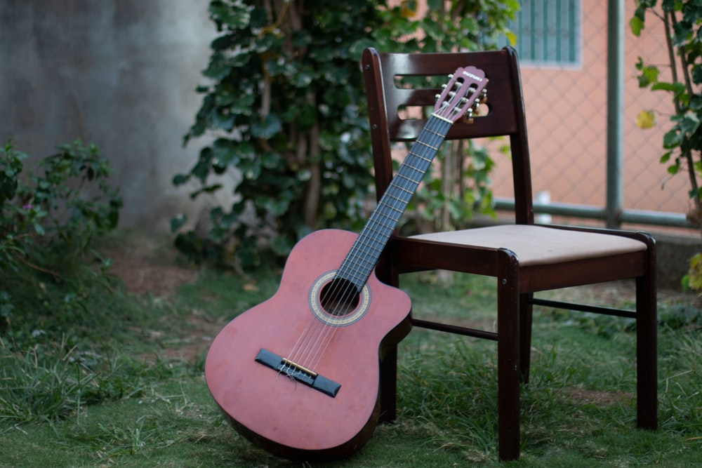 red acoustic guitar on brown wooden table