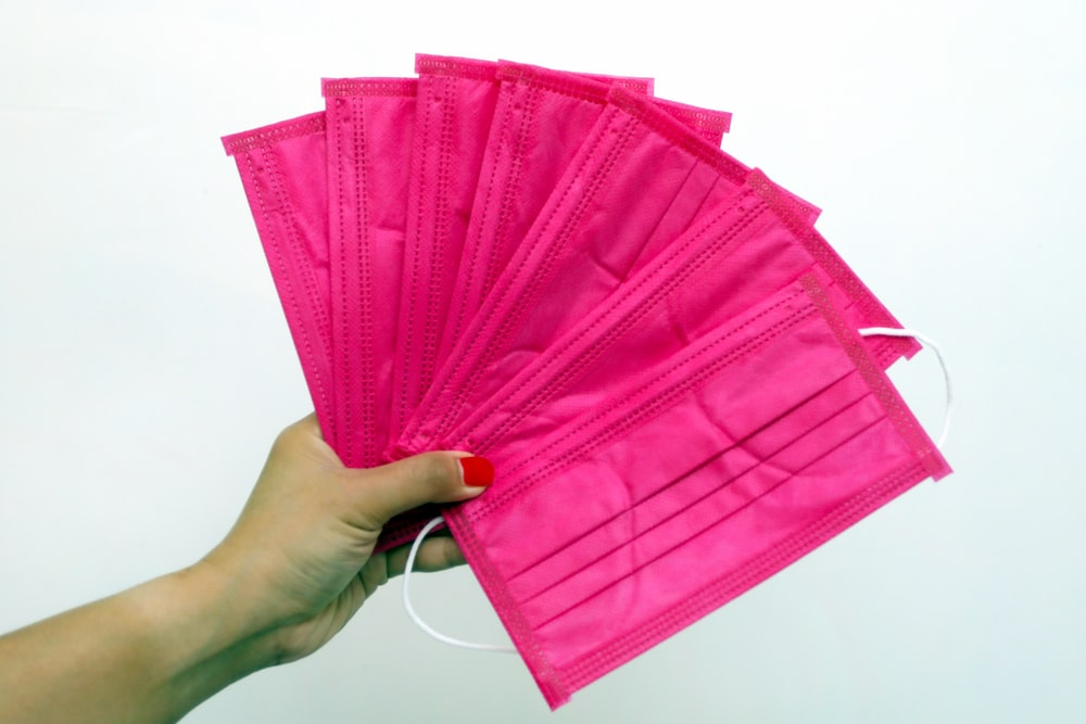 person holding pink plastic bag