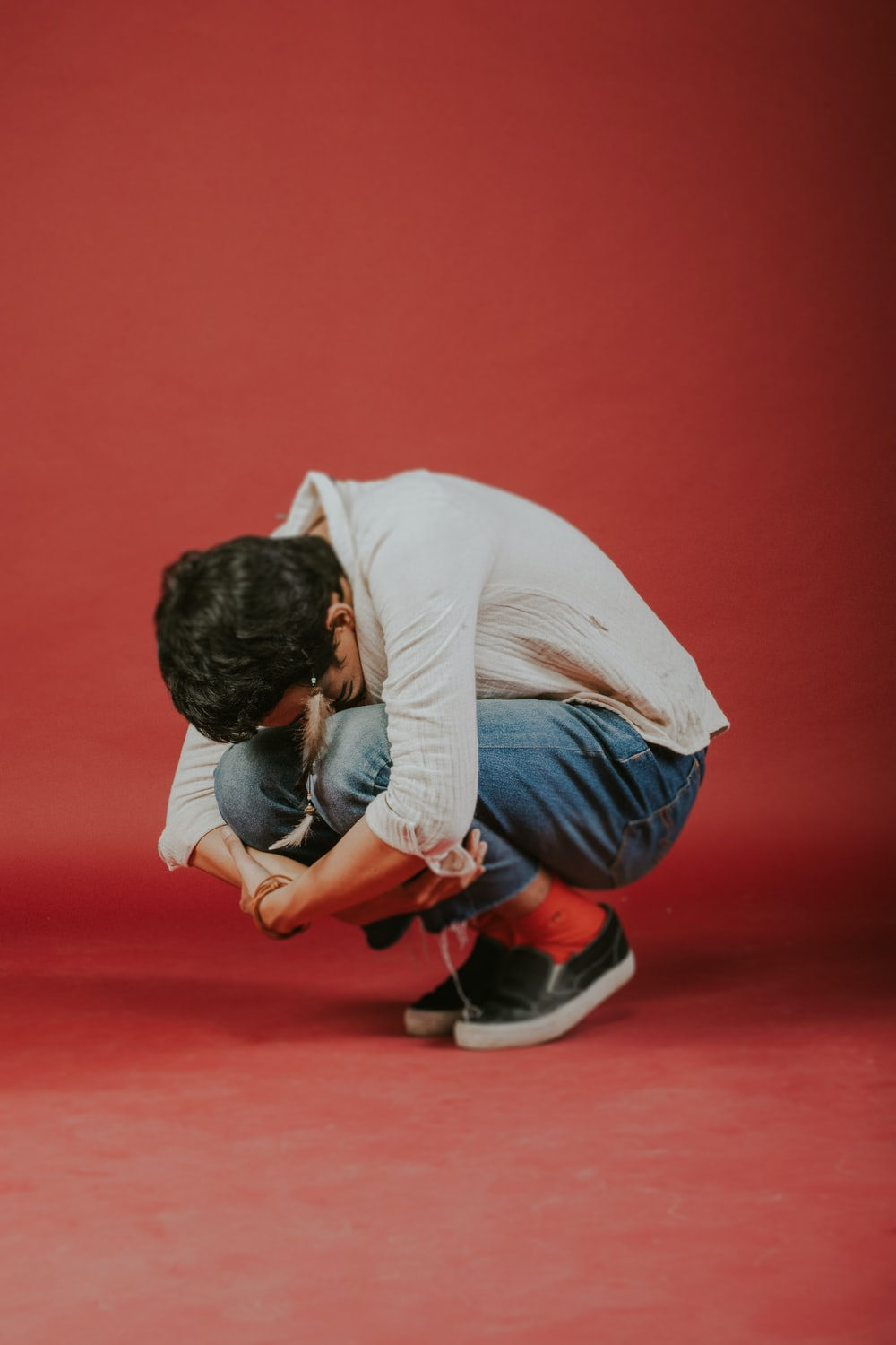 man in white long sleeve shirt and blue denim jeans sitting on red floor