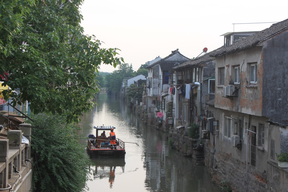 people riding boat on river between buildings during daytime