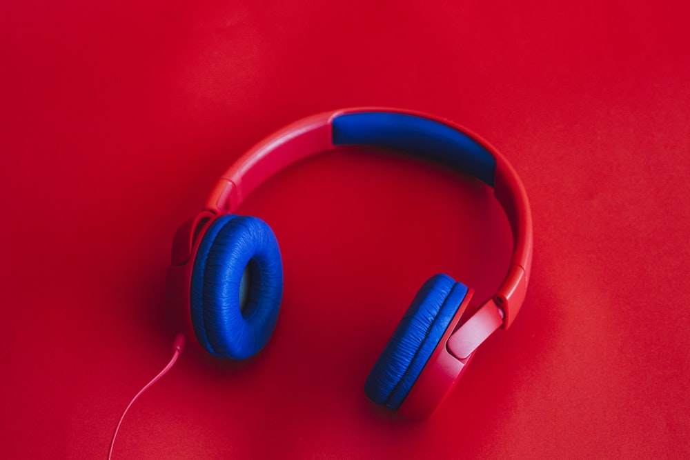 blue and black headphones on red surface
