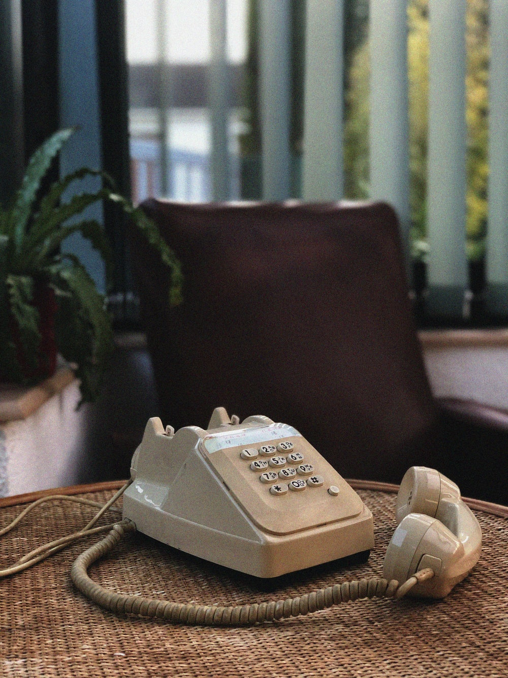 white and gray ip desk phone on brown wooden table