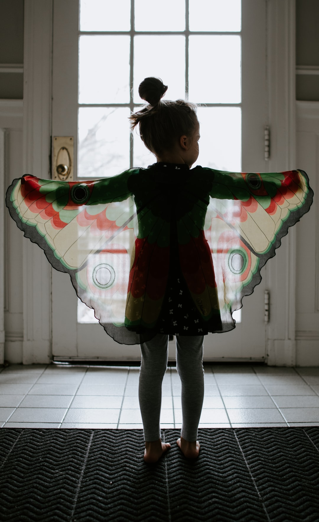 Little girl standing in a doorway with butterfly wings
