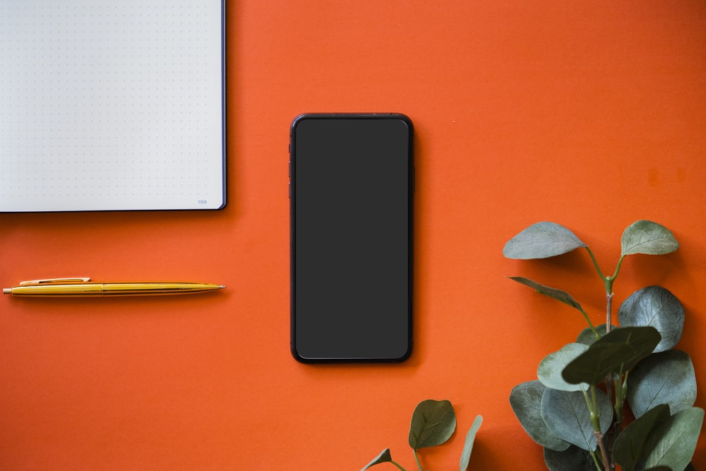 black iphone 5 on orange surface