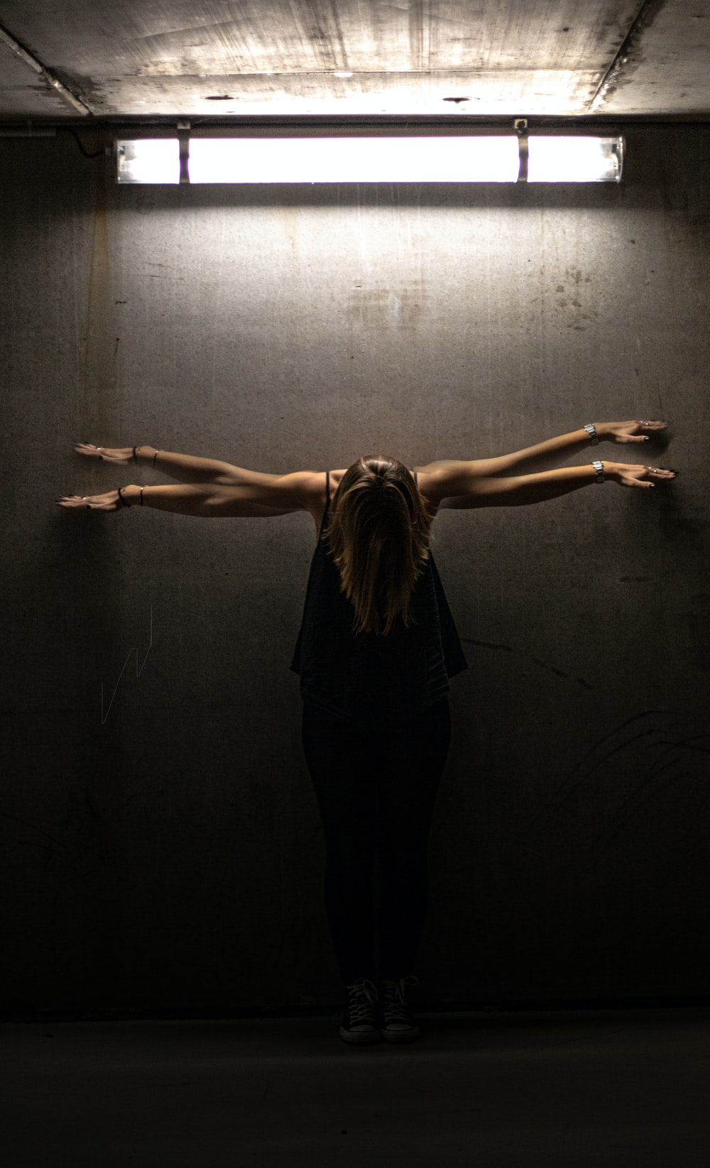 woman in black tank top and black pants standing on gray wall