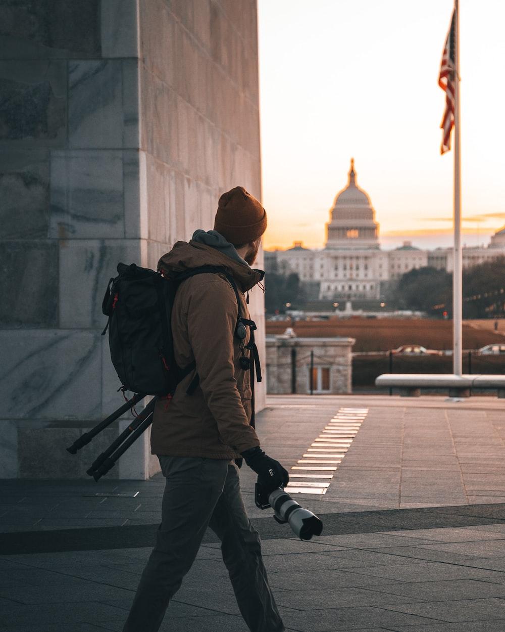 man in brown jacket and black pants wearing brown knit cap walking on sidewalk during daytime
