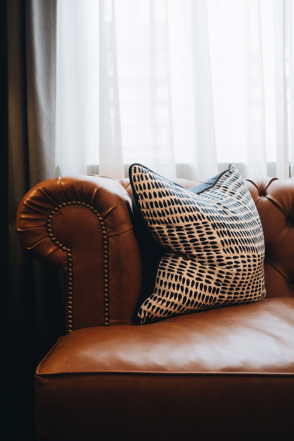 brown and white throw pillow on brown leather couch