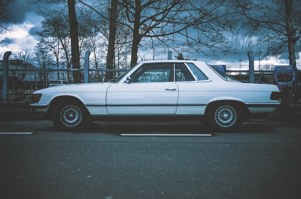 white sedan parked on gray asphalt road during daytime