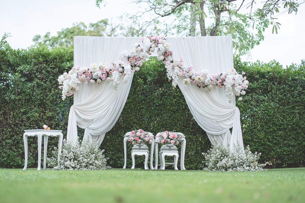 white and pink flower bouquet on white wooden armchair